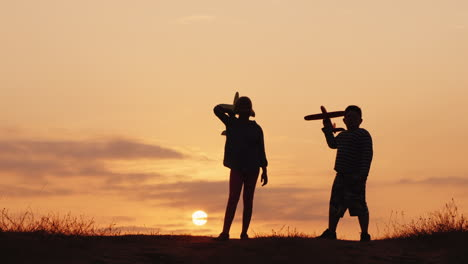 Silhouettes-Of-A-Girl-And-A-Boy-Playing-Together-With-Airplanes-At-Sunset-A-Happy-And-Carefree-Niño