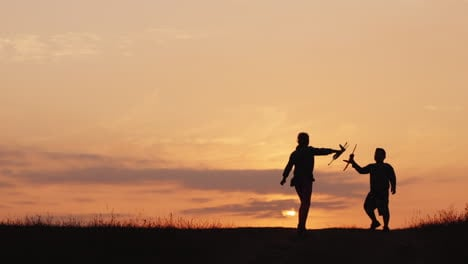 Silhouettes-Of-A-Girl-And-A-Boy-Playing-Together-With-Airplanes-At-Sunset-A-Happy-And-Carefree-Child
