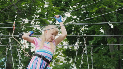 A-Brave-Girl-Moves-Along-The-Ropes-Between-The-Trees-Uses-A-Safety-Rope