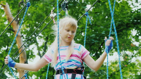 Rear-View-Of-A-Brave-Girl-Moves-Along-The-Ropes-Between-The-Trees-Uses-A-Safety-Rope