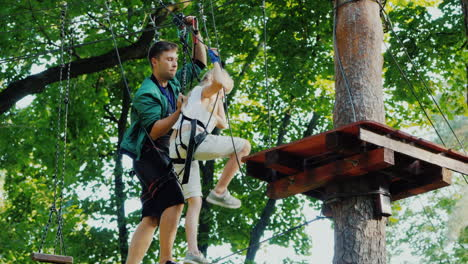 Instructor-Helps-Child-In-Maze-Of-Ropes-High-In-Tree-Branches
