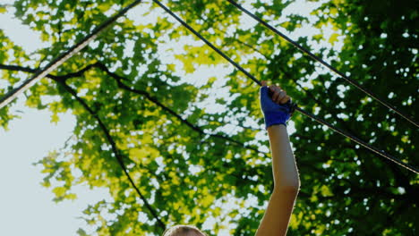 Active-Child-Fearlessly-Climbs-The-Ropes-Between-The-Trees