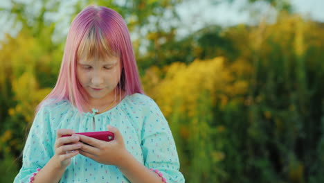 The-Child-Uses-A-Smartphone-The-Girl-With-Pink-Hair-And-A-Pink-Phone-In-Her-Hands