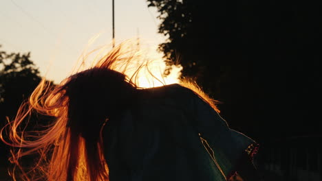 Girl-With-Long-Hair-Having-Fun-At-Sunset-Waving-Her-Head-Playing-With-Her-Hair-In-The-Sun-s-Rays