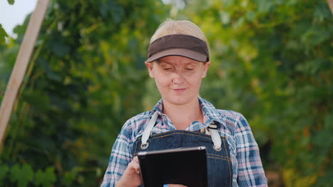 Woman-Farmer-Uses-A-Tablet-Against-The-Background-Of-A-Well-Maintained-Vineyard