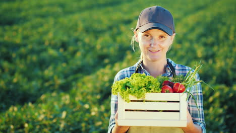 Portrait-Of-A-Female-Farmer-Standing-In-The-Field-Holding-A-Box-With-A-Set-Of-Fresh-Vegetables-Organ
