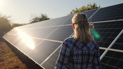 A-Woman-Walks-Along-The-Solar-Panels-Of-A-Small-Home-Solar-Power-Plant