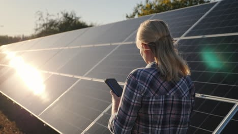 Woman-With-Smartphone-Goes-Aquarius-Solar-Panels-At-Home-Solar-Power-Plant