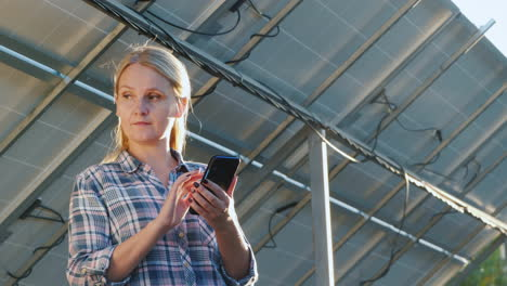 The-Woman-Uses-A-Smartphone-Stands-At-The-Inverter-Under-The-Panels-Of-The-House