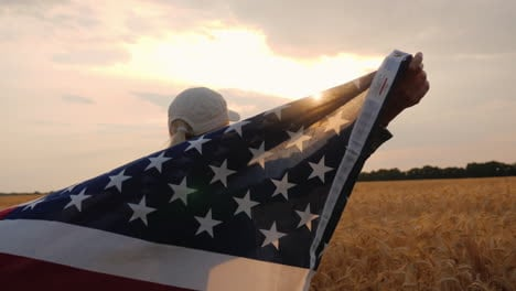 Farmer-With-American-Flag-Stands-In-A-Wheat-Field
