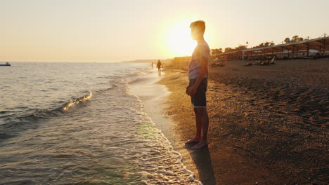 Young-Man-Stands-On-The-Beach-Admires-The-Sunset