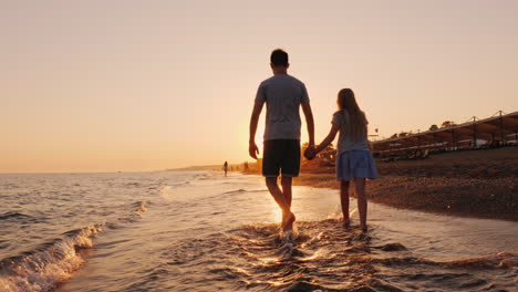 Brother-And-Younger-Sister-Walking-Along-The-Surf-Line-On-The-Beach-At-Sunset