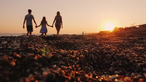 Young-Family-With-A-Child-Walking-Along-The-Beach-At-Sunset-In-The-Foreground-A-Pebble-Beach