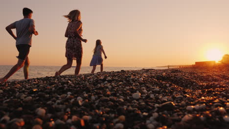 A-Family-With-A-Child-Jogs-Along-The-Surf-Line-To-The-Sea-At-Sunset