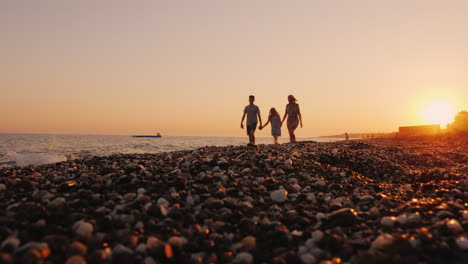 Family-With-A-Child-Walking-At-Sunset-At-The-Seashore-Relaxing-Together-At-A-Resort