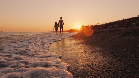 Brother-And-Younger-Sister-Walking-Along-The-Seashore-At-Sunset