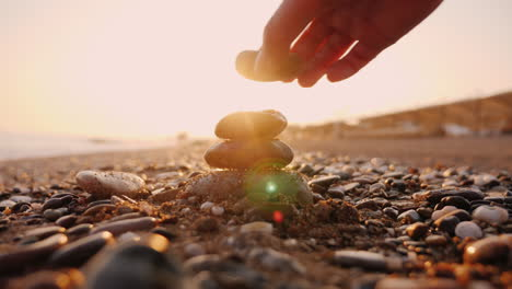 Hand-Puts-Stones-In-The-Pyramid-The-Sun-s-Rays-Shine-Through-His-Fingers