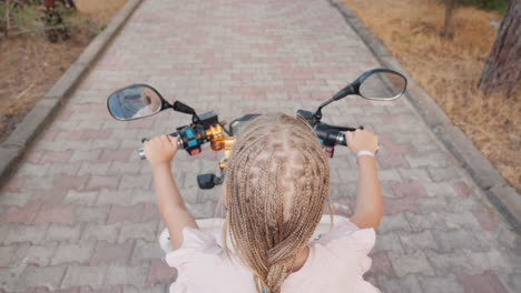A-Child-With-African-Pigtails-Riding-A-Scooter-Rear-View-Cheerful-And-Active-Recreation