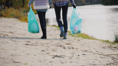 Woman-Volunteer-With-A-Child-Walk-Along-The-Lake-Carry-Packages-With-Garbage