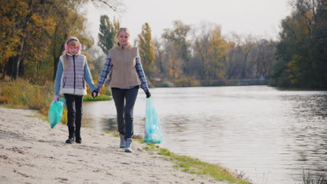 Woman-Volunteer-With-A-Niño-Walk-Along-The-Lake-Carry-Packages-With-Garbage