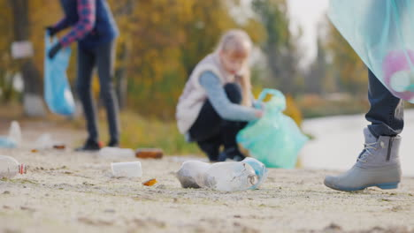 A-Group-Of-Volunteers-Picks-Up-Trash-On-The-Lake-Stacks-Plastic-Waste-In-Bags