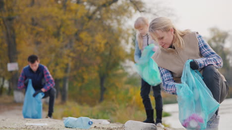 A-Young-Woman-With-Children-Collect-Garbage-Along-The-Lake-Put-Plastic-Waste-In-Bags