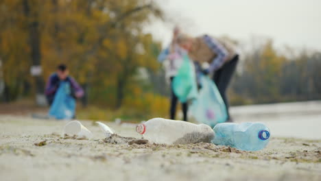 Active-People-Clean-The-Shore-Of-Garbage-In-The-Foreground-Are-Discarded-Plastic-Bottles-Caring-For-