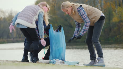 A-Woman-With-Children-Picks-Up-Trash-On-The-Lake-Volunteers-Collect-Plastic-Waste