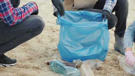 People-Put-Trash-From-The-Beach-In-A-Bag-Garbage-Collection-Environmental-Care-Close-Up-Shot
