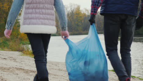 Children-Volunteers-Carry-A-Bag-Of-Garbage-Go-Along-The-Shore-Of-The-Lake-Where-They-Collected-Waste