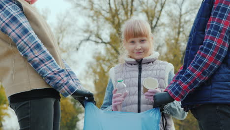 Child-Volunteer-Collects-Trash-In-The-Park-Smiling-At-The-Camera