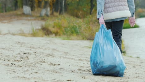 The-Girl-Carries-A-Heavy-Bag-With-Garbage-Park-Cleaning-And-Environmental-Care