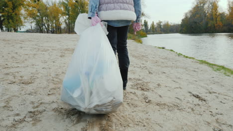 A-Volunteer-Child-Drags-A-Heavy-Garbage-Bag-Along-The-Beach-Cleaning-Of-Waste-And-Activism-Follow-Sh