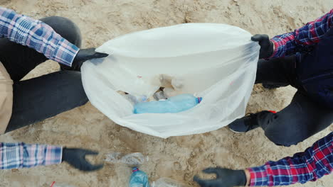 Volunteers-Put-Plastic-Trash-In-A-Bag-Cleaning-The-Beach-Taking-Care-Of-The-Environment
