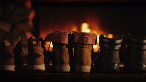 A-Few-Pairs-Of-Winter-Shoes-Are-Drying-Near-The-Fireplace-Where-The-Fire-Is-On