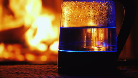 Water-Boils-In-A-Backlit-Electric-Kettle-A-Fire-In-The-Background-Burns-In-The-Background