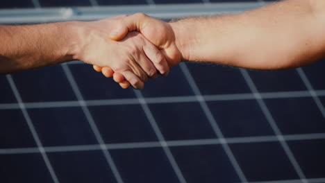 Handshake-Of-Two-Men-On-The-Background-Of-Solar-Panels