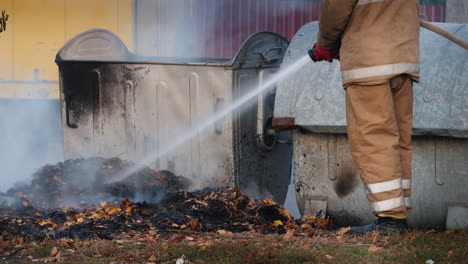 Firefighter-Puts-Out-A-Fire-Near-Garbage-Bins-After-A-Riot