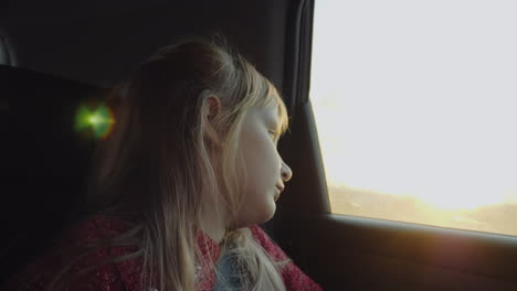 A-Child-Looks-Out-The-Car-Window-Travels-In-The-Back-Passenger-Seat