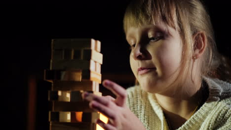 Portrait-Of-A-Child-Playing-A-Game-Where-You-Need-To-Take-Out-Wooden-Blocks-From-The-Tower