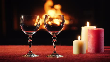 Two-Empty-Wine-Glasses-Candles-And-A-Fireplace-In-The-Background-Are-Burning-Nearby