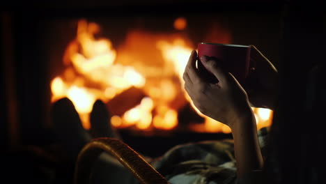 Tea-By-The-Fireplace---Female-Hands-With-A-Red-Cup-On-The-Background-Of-The-Fireplace-Where-The-Fire