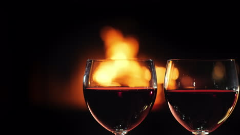 Two-Glasses-Of-Red-Wine-Against-The-Background-Of-The-Fireplace-Where-The-Fire-Burns