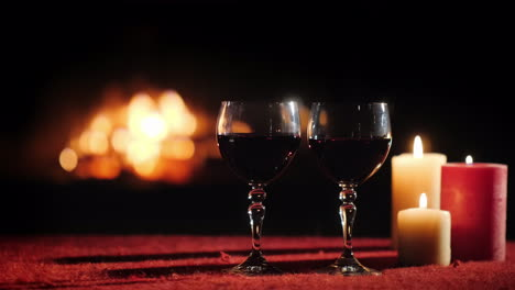 Glasses-Of-Wine-And-Candles-On-A-Table-With-A-Red-Tablecloth-In-The-Background-A-Fireplace