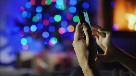 Hands-With-Smartphone-On-Blurry-Lights-Of-Christmas-Tree-And-Fireplace-Gift-Order