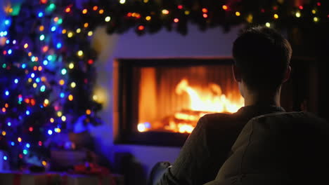 A-Young-Man-Admires-The-Fire-In-The-Fireplace-Which-Is-Decorated-With-Garlands-For-Christmas