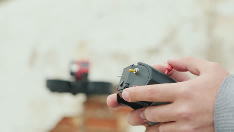 Hands-Of-The-Pilot-Of-The-Cinedrone-With-The-Control-Panel-In-The-Background-You-Can-See-A-Flying-Dr