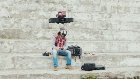 A-Man-In-A-Helmet-With-Telemetry-Controls-A-Drone-That-Flies-In-Front-Of-Him
