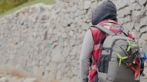 A-Man-With-A-Backpack-Behind-Him-And-A-Sports-Drone-Walks-Along-A-Stone-Wall