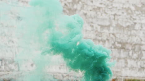 Green-Smoke-On-The-Background-Of-An-Old-Brick-Wall-In-White